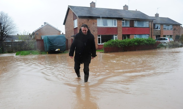 A damp day for Stewart Barber as he walks through flood water near his home in Northallerton, North Yorkshire as the heavy rain spread north.