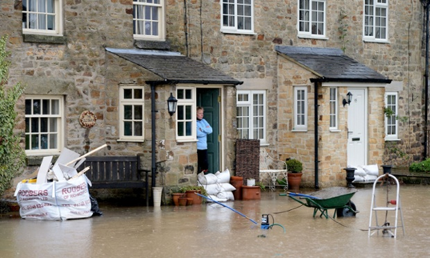 Rubble from the last flood stands piled outside houses in Gilling West near Richmond, north Yorkshire as residents pile up sandbags to try and prevent a repeat of the damage as floodwaters rise in the village today.