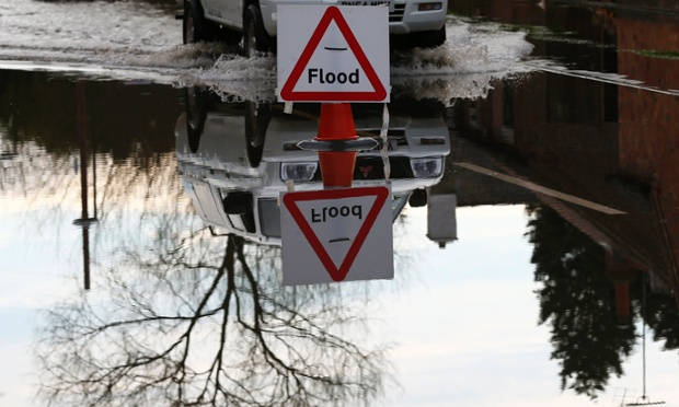 The sign says it all. A car makes its way through flood water from the River Trent in Willington.
