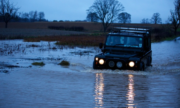 The sun begins to set as a Land Rover rescues a group of disabled adults, cut off by floodwater at their workshops at Newby Hall, Ripon, North Yorkshire.
