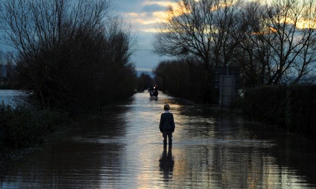 A boy watches horse riders on a flooded road near Moorland, Somerset.