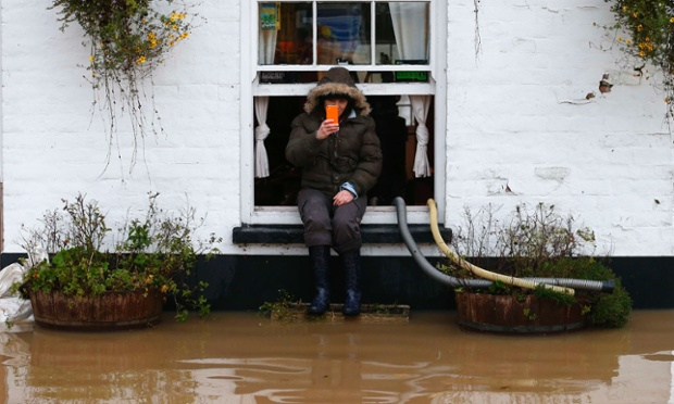 Amy Guy sits on a windowsill of the flooded White Bear pub in Tewkesbury.