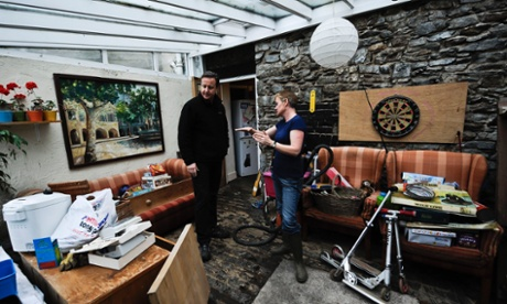 Prime Minister David Cameron listens as resident Musky Kendall, in Buckfastleigh, near Exeter, explains how the floods quickly rose inside her house during the recent floods.