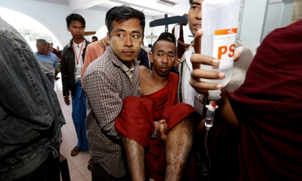 An injured monk is carried into the Monywa hospital after being injured when police fired water cannon, tear gas and firebombs on a demonstration outside the Latpadantaung copper mine in the Sagaing division near Monywa in Burma.