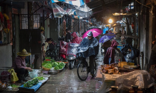Shoppers brave torrential rain in a street market bustling with daily life in Chaozhou in Guangdong province, China.
