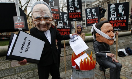 A campaigner wearing a giant mask depicting Rupert Murdoch pretends to burn the Leveson report while  another wearing a David Cameron mask sits tied to a chair on 29 November 2012.
