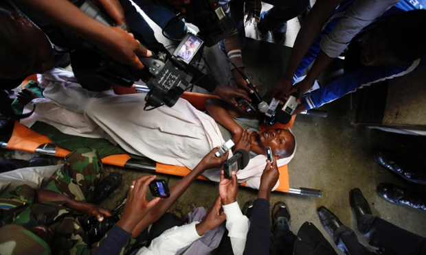 Journalists interview a wounded rebel fighter at a military base in Muti village west of the Rwandan capital Kigali. Troops clashed with Rwandan FDLR rebels who attacked three villages on its border with Democratic Republic of Congo, according to reports.