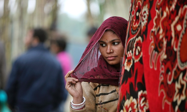 A woman waits to offer prayers at a Hindu temple during the Jhiri fair at Kanachack village on the outskirts of Jammu, India. According to legend, the fair is held in memory of Baba Jitu, an honest farmer who killed himself since he was not prepared to submit to the unjust demands of a landlord who wanted him to part with his crop.