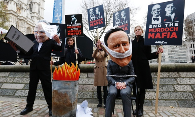 Protesters dressed as Rupert Murdoch and David Cameron demonstrate outside the venue where Lord Justice Leveson is releasing his report on media practices in central London.