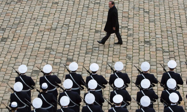 On guard: French President Francois Hollande reviews troops during a military ceremony at the Hotel des Invalides in Paris, France.