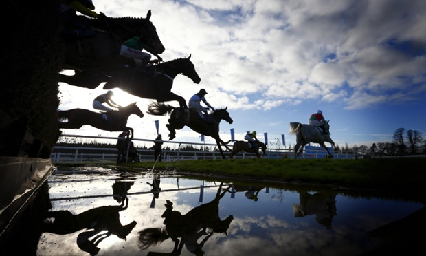 Paddy Brennan on Parsnip Pete (4) is seen almost in silhouette under a low winter sun leaping the water with the field before winning the Burges Salmon Novices' Handicap Steeple Chase at Newbury Racecourse.