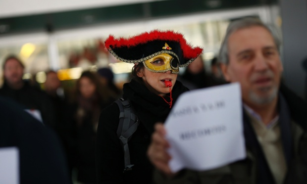 A masked demonstrator takes part in a protest outside Madrid's Barajas airport. Spanish airline Iberia's ground and cabin crews will stage a series of strikes in December, disrupting the holiday travel season to protest against massive job cuts.