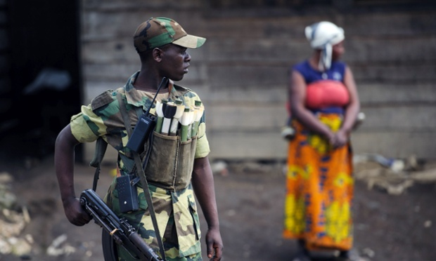 An M23 rebel stands in the town of Mushaki in the Democratic Republic of Congo. The rebel fighters in the eastern DRC have agreed to hand over the frontline town of Sake tomorrow to UN and regional officials and the key city of Goma is to follow.