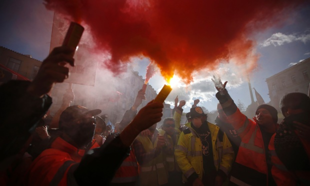 Dockers hold up flares during a protest in front of Portugal's parliament in Lisbon. Hundreds of dockworkers from countries across Europe joined the protest in Lisbon against plans by the Portuguese government to change labour rules in the sector.