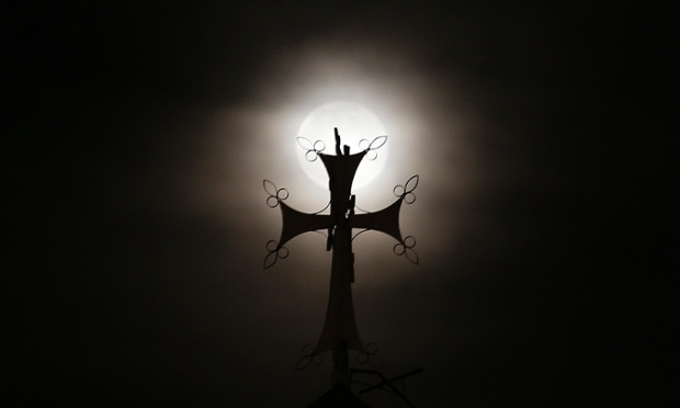 The full moon rises behind a crucifix on a church in Beirut, Lebanon.