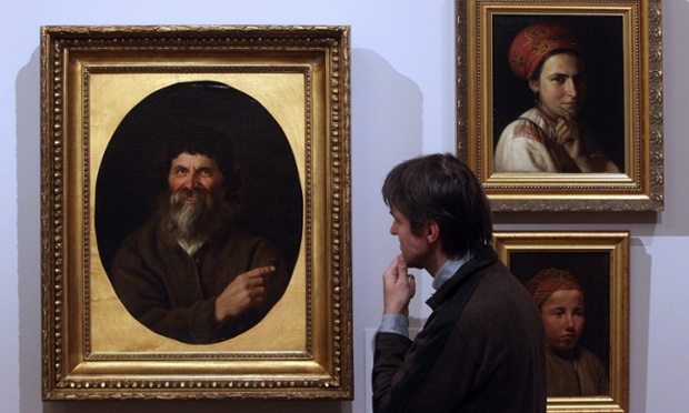 A visitor examines paintings at the Faces of Russia exhibition, showing at the Russian Museum in St. Petersburg.