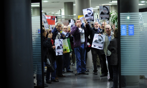 Protesters hold placards inside a Caixa bank office in Barcelona during a demonstration against preference shares in which investors are asking the bank to return their savings.