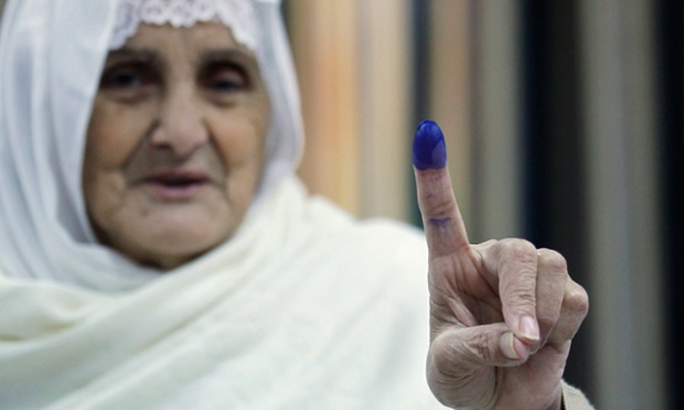 An Algerian woman shows her ink-stained finger after casting her ballot for the regional and municipal elections at a polling station in Algiers.