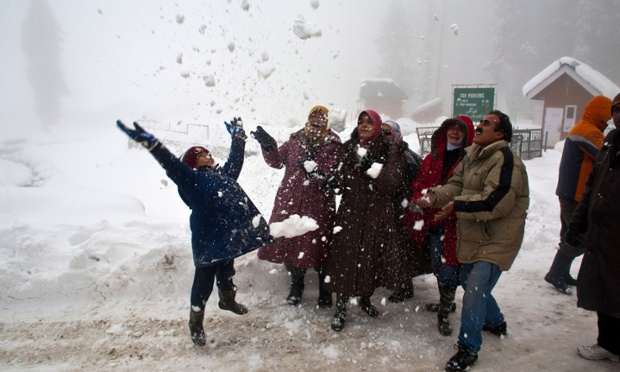 A group of Malaysian tourists play during the season's first snowfall in Gulmarg, Kashmir.