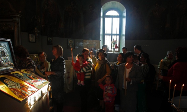 Members of Romania's Roma ethnic minority attend a rare mass Orthodox baptism ceremony at a church in Slobozia, 81 miles east of Bucharest.