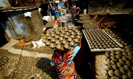 A woman carries freshly formed earthen lamps for drying outside her home in Mumbai, India.