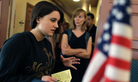 College student Paige McLoughlin, 19, of Parker, Colorado, talks over paperwork with an electoral official before voting.