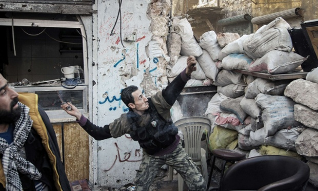 A rebel fighter throws a grenade towards a Syrian government forces position down an alleyway in the northern Syrian city of Aleppo.