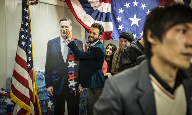 An Afghan journalist gestures with a cardboard cut-out of Mitt Romney at the US embassy in Kabul, Afghanistan.