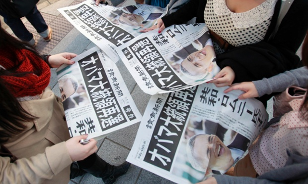 People read extra editions of newspapers reporting President Barack Obama's re-election in Tokyo.