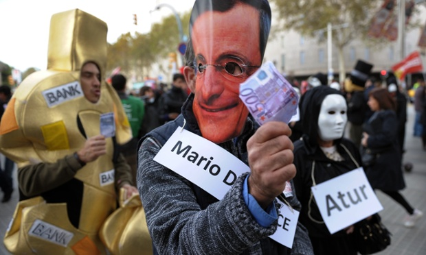 A demonstrator wearing a mask of European Central Bank President Mario Draghi waves a five-hundred euro note outside the headquarters of the Bank of Spain in Barcelona during a demonstration by bank employees.