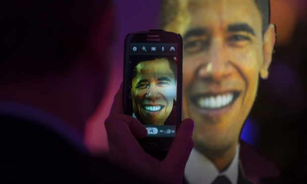 A man takes a photo of a life-size cutout of President Barack Obama at an election party at the US embassy in Berlin.