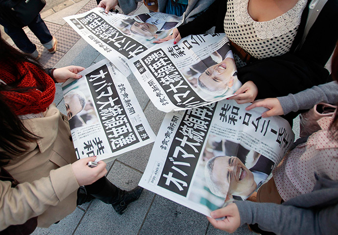 World election reaction: Tokyo, Japan: People read newspapers reporting Barack Obamas re-election