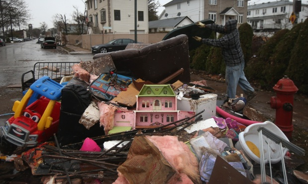 Richie Bain throws household belongings into a garbage pile while helping a friend clean his flood-damaged home in the Staten Island borough of New York City.