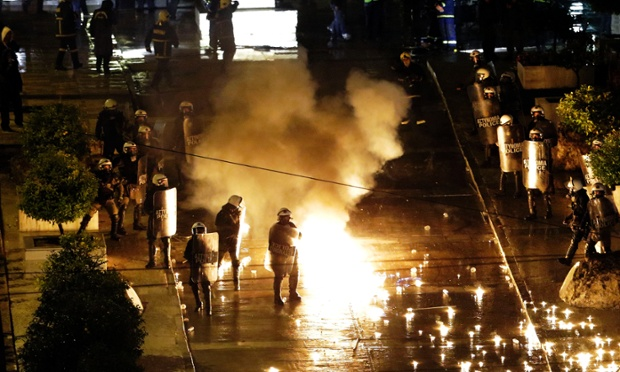 A petrol bomb thrown by protesters explodes near riot police in front of parliament during clashes in Athens, Wednesday Nov. 7, 2012.