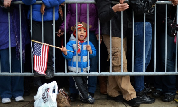 A young boy holds a US flag as supporters wait to catch a glimpse of US President Barack Obama's motorcade near his house in Chicago.