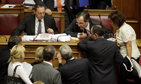 Greek Finance Minister Yannis Stournaras (Top L) looks on as ministers speak with Greek Prime Minister Antonis Samaras (Top 3rd R) at the end of a session of the Greek parliament dedicated to new austerity measures, in Athens on November 7, 2012.