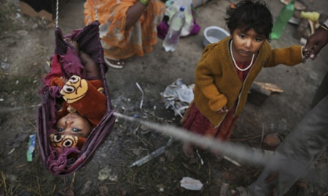 Indian baby Priya hangs in a makeshift bed as her sister stands next to her at a shanty where their family lives New Delhi, India.