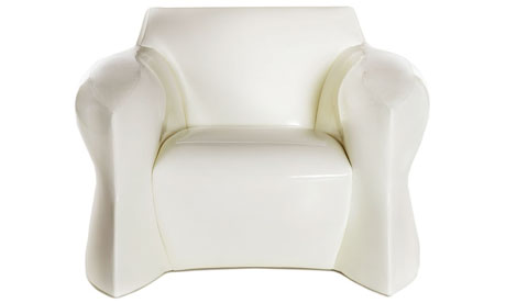 A curvaceous armchair upholstered in white patent leather