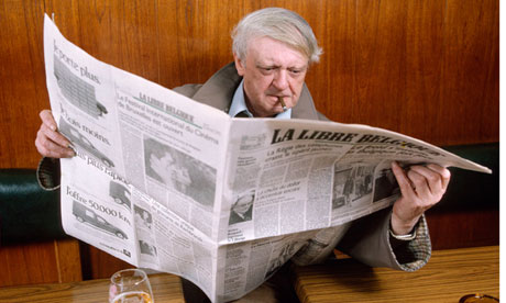 Anthony Burgess reading Belgian newspaper La Libre Belgique while smoking