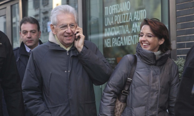 Italian premier Mario Monti takes a call on his mobile phone as he walks through a Milan street wit