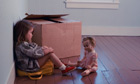 Little brown haired girl sitting on a suitcase in an empty room with one box and staring at her doll