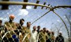 Iraqi prisoners stand behind razor wire