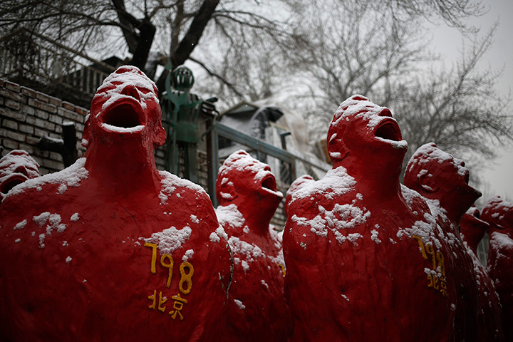 24 hours: Beijing, China: Snow falls on sculptures
