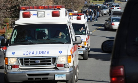Ambulances leave an area near the scene of a shooting at the Sandy Hook elementary school in Newtown, Connecticut.