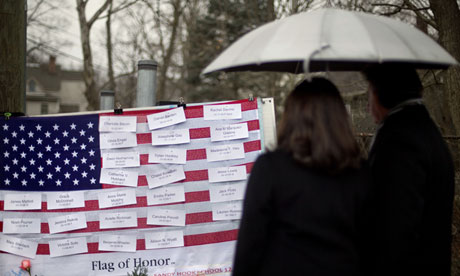 Mourners looks at the names on a US flag of the Sandy Hook elementary