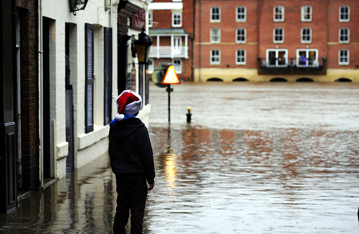 Wet weather: A young Christmas shopper looks at floodwater in York city centre