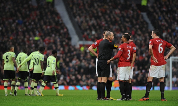 Mike Dean explains to Manchester United's players why he decided that Newcastle's second goal, originally disallowed, should stand after all.