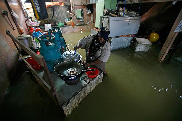 24小时的图片:一位村民准备在她淹没房子在Rantau班让食物