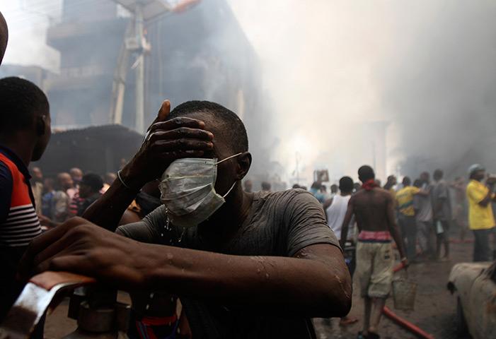 图说24小时:志愿者清理他的脸在工地附近的一把火,尼日利亚