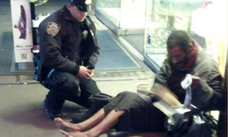 New York police officer Larry DePrimo gives a homeless man a pair of boots and socks in Times Square